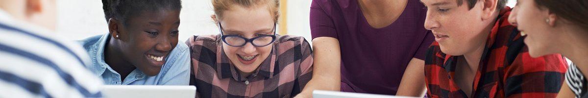 Leerlingen in digitaal klaslokaal met pc's en tablet