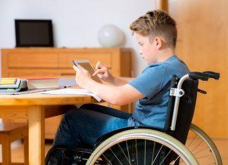 jongen in rolstoel doet huiswerk op tabelt