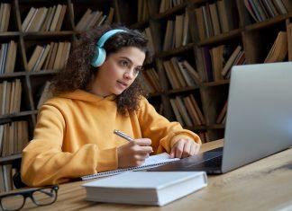 Meisje met headphone en pc doet schoolwerk thuis