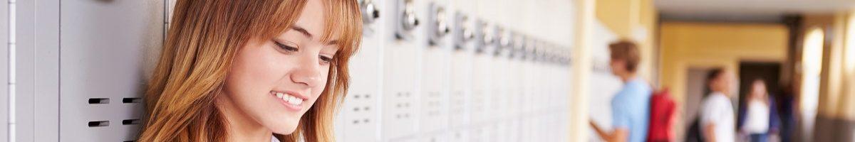 scholiere met mobiele telefoon voor lockers
