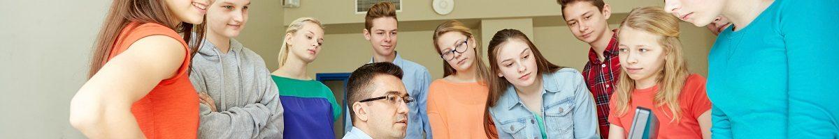Leerlingen staan rond leraar die informatie op computer deelt